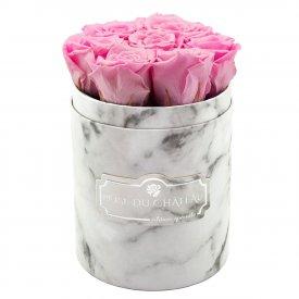 Světle růžové věčné růže v malém bílém mramorovém flowerboxu