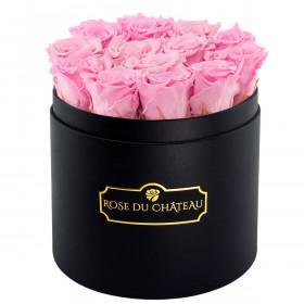 Světle růžové věčné růže v černém kulatém flowerboxu